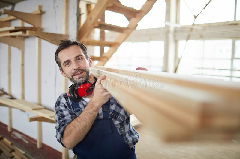 Mature Builder carrying Wooden Boards stock photo