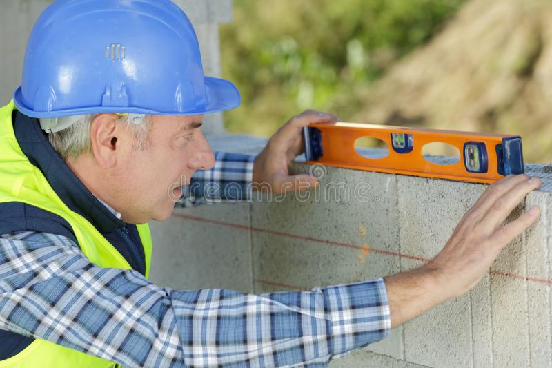 Mature builder levelling wall. Mature builder levelling a wall royalty free stock image