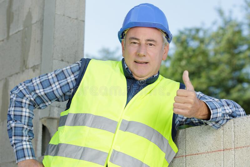 Mature builder showing thumb-up stock image