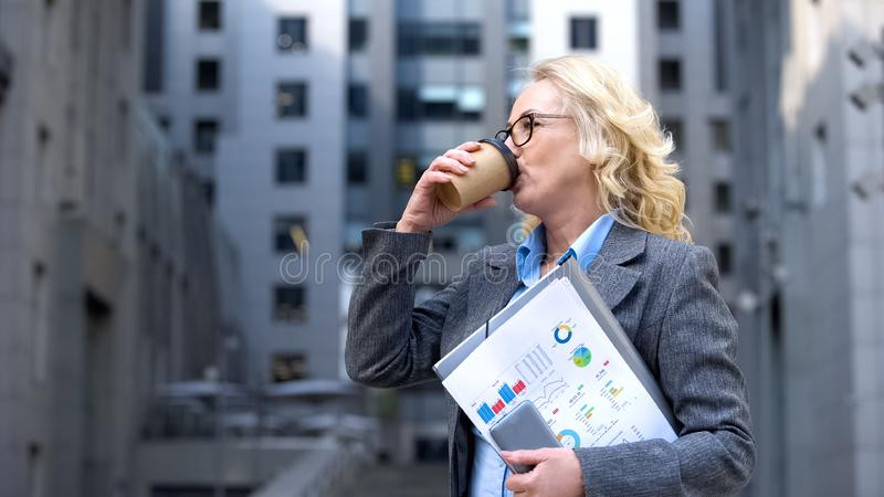 Mature business lady with documents in hand drinking coffee, morning energy stock images