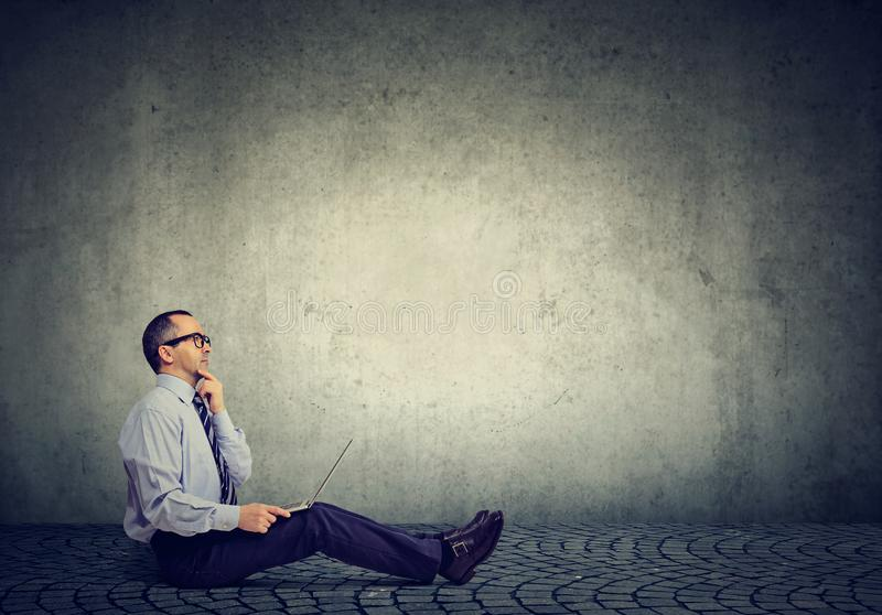 Mature business man with laptop sitting on a floor thinking stock photos