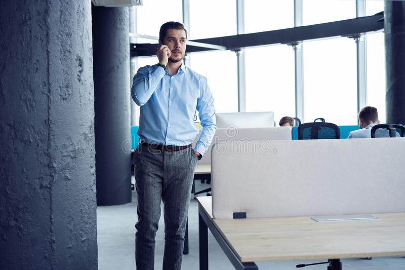 Mature business man standing inside office building and using cell phone. royalty free stock photo