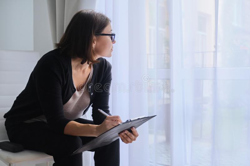 Mature business woman with clipboard looking out the window stock images