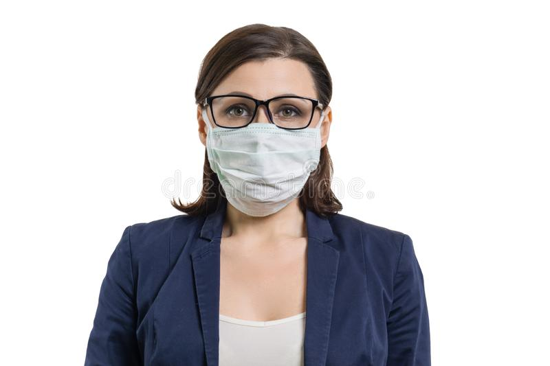 Mature business woman in glasses and protective medical mask looking at camera . White background isolated royalty free stock image