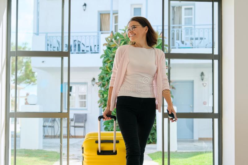 Mature business woman in hotel interior with suitcase stock images