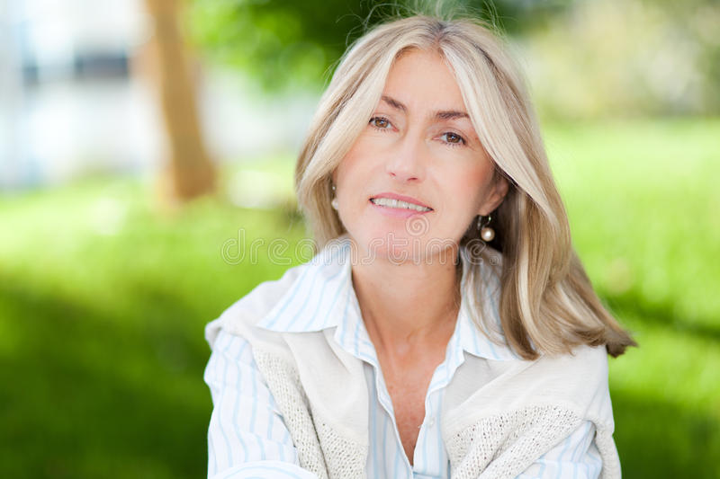 Mature business woman sitting outdoor royalty free stock photos