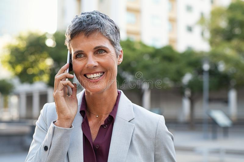 Mature business woman talking on phone outdoor stock photography