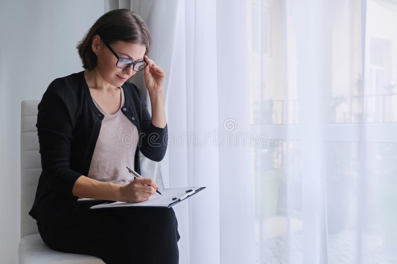 Mature business woman writing on business papers royalty free stock images