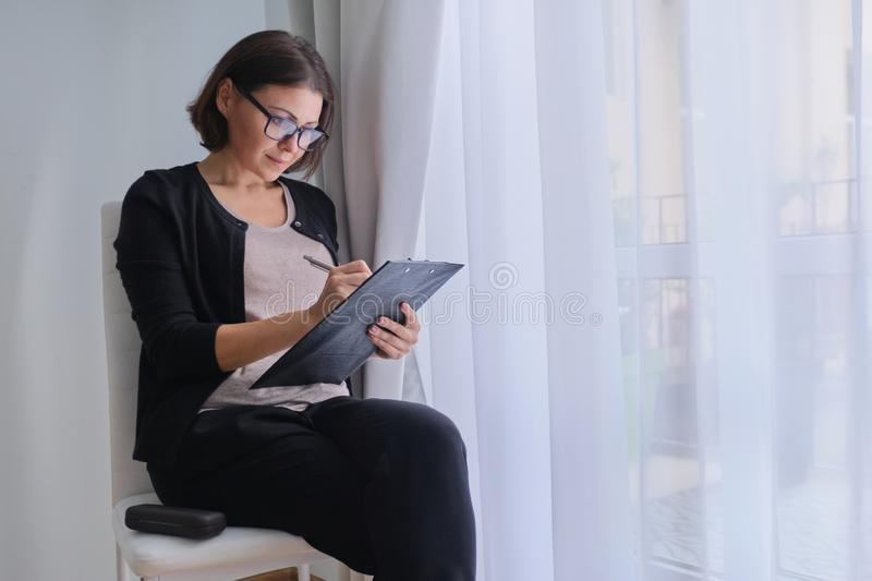 Mature business woman writing on business papers stock images