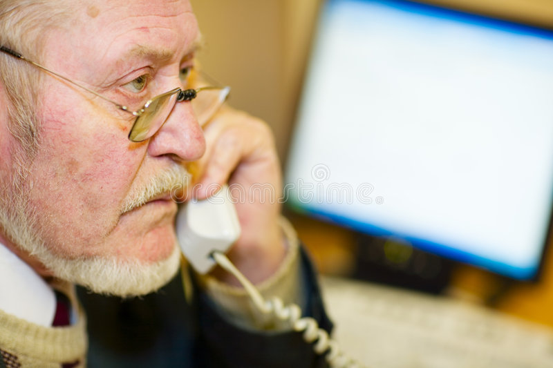 Mature businessman. Talking on the phone, checking out a document on his computer monitor stock photo