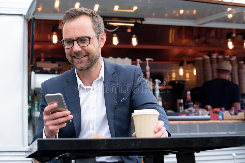 Mature Businessman Checking Mobile Phone Sitting At Outdoor Coffee Shop royalty free stock image