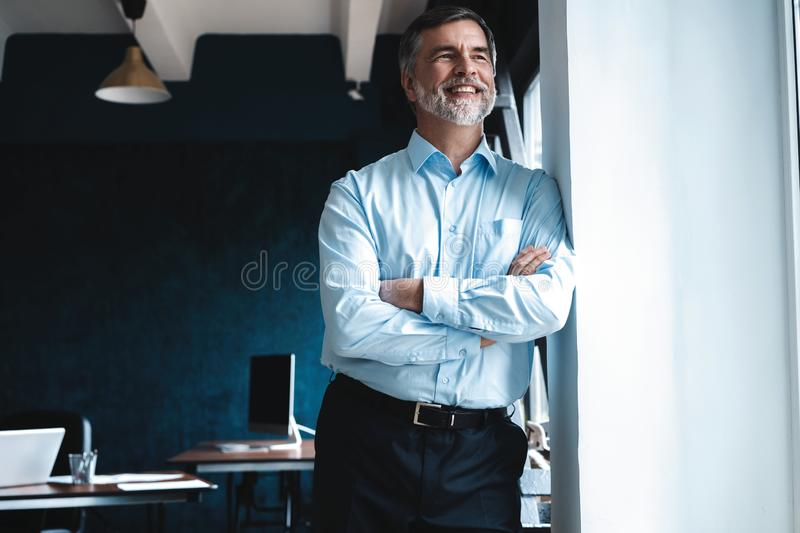 Mature businessman in a corporate suit standing in office and looking away through large windows optimistically. stock image