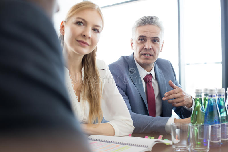 Mature businessman discussing with colleagues at conference table in office.  stock images