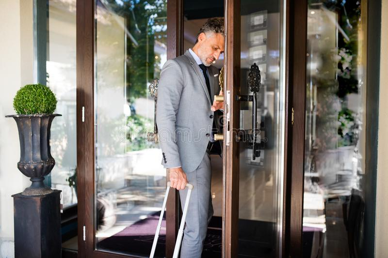 Mature businessman entering hotel with luggage. Man opening the hotel front door stock photo