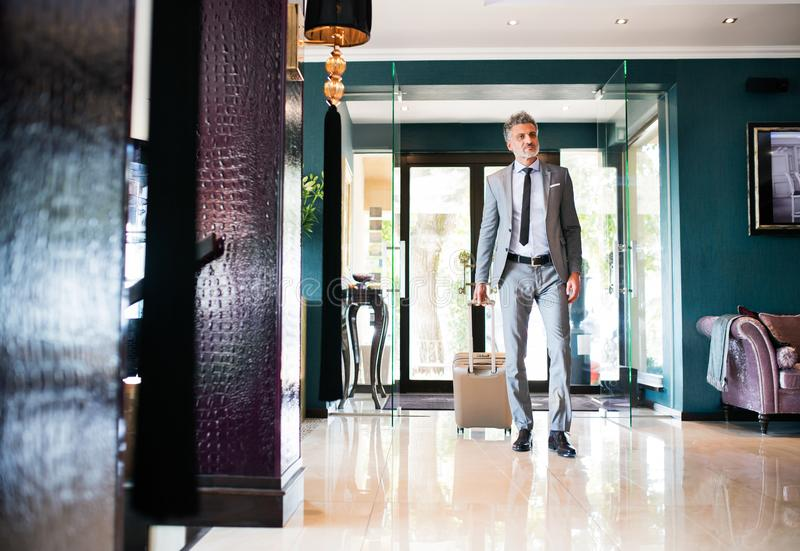 Mature businessman entering hotel with luggage. Mature businessman entering or leaving hotel with luggage. Man walking in the hotel entrance hall royalty free stock photo