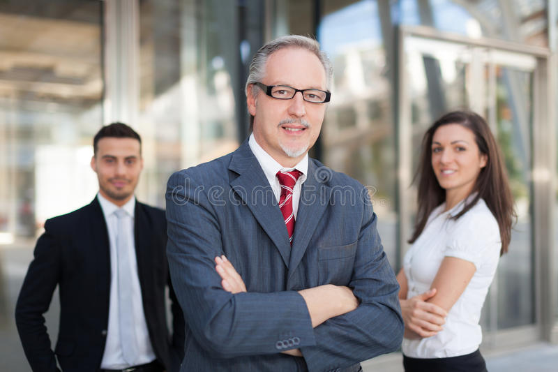 Mature businessman in front of a group of business people outdoor stock images