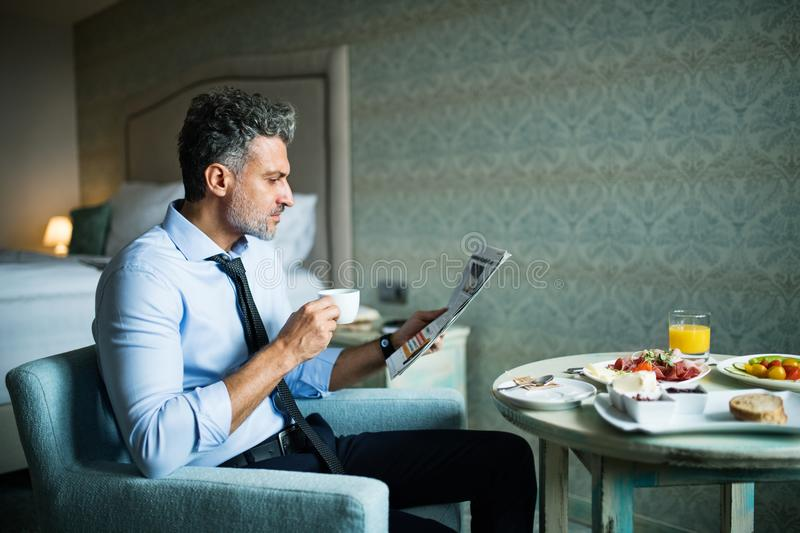 Mature businessman having breakfast in a hotel room. Mature, handsome businessman having breakfast in a hotel room, reading newspapers and drinking coffee royalty free stock images