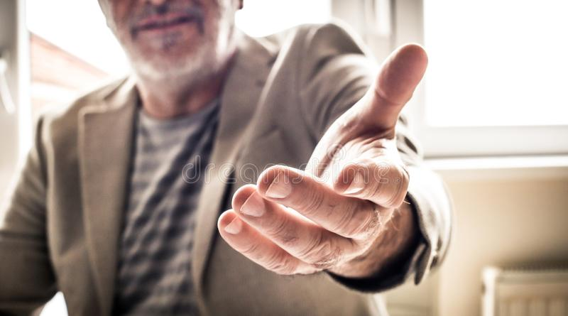 Mature businessman helping hand. Close up. royalty free stock image