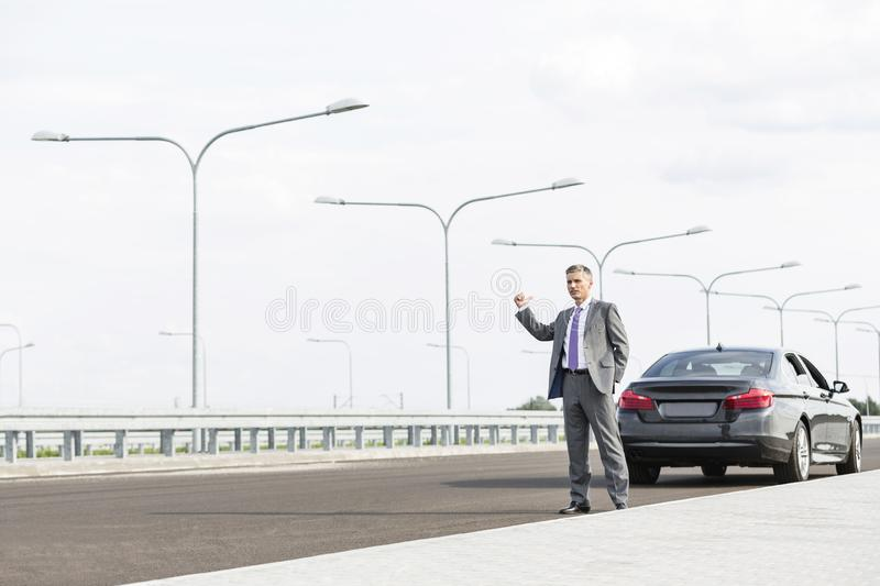 Mature businessman hitchhiking while standing with breakdown car on road stock photo