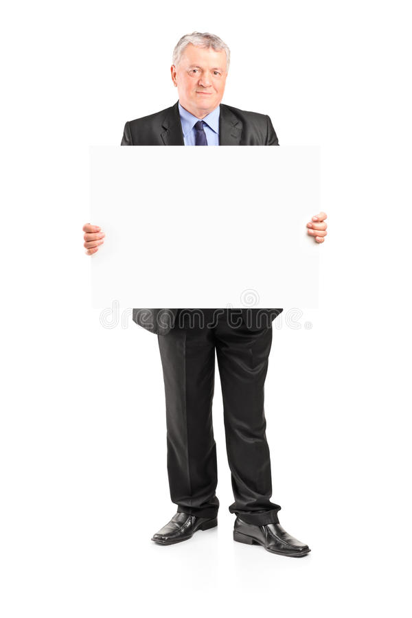 Mature businessman holding a blank poster. Full length portrait of a mature businessman holding a blank poster isolated on white background royalty free stock photos