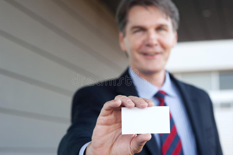 Mature businessman holding business card royalty free stock photo