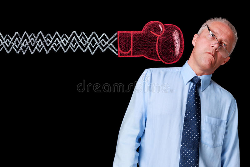 Mature businessman knockout punch. Photo of a mature businessman against a black background being delivered a knockout punch by a handrawn chalk boxing glove on royalty free stock photo