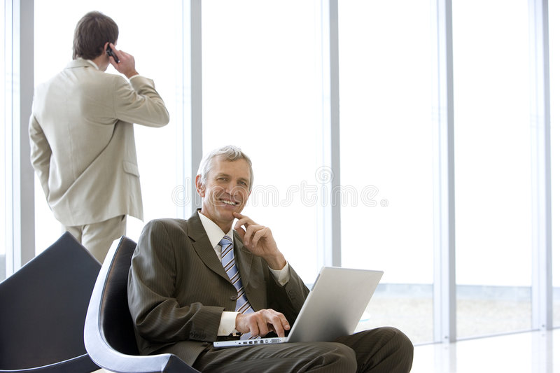 Mature businessman with laptop. And colleague on cell phone
