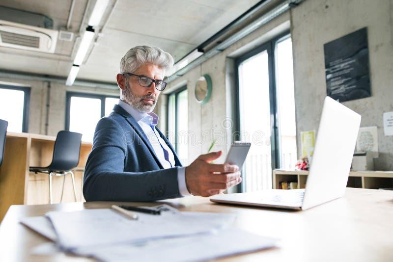 Mature businessman with laptop and smart phone. stock photos