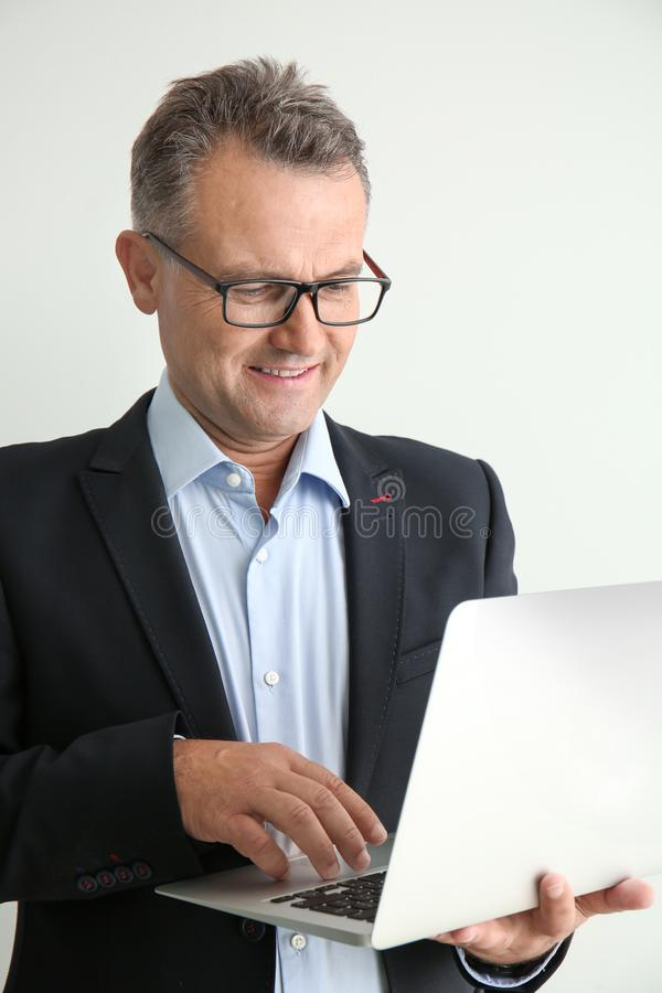 Mature businessman with laptop on white background stock photos