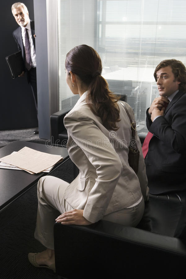 Mature businessman leaning out of office, calling businesswoman to interview, woman rising from sofa royalty free stock photography