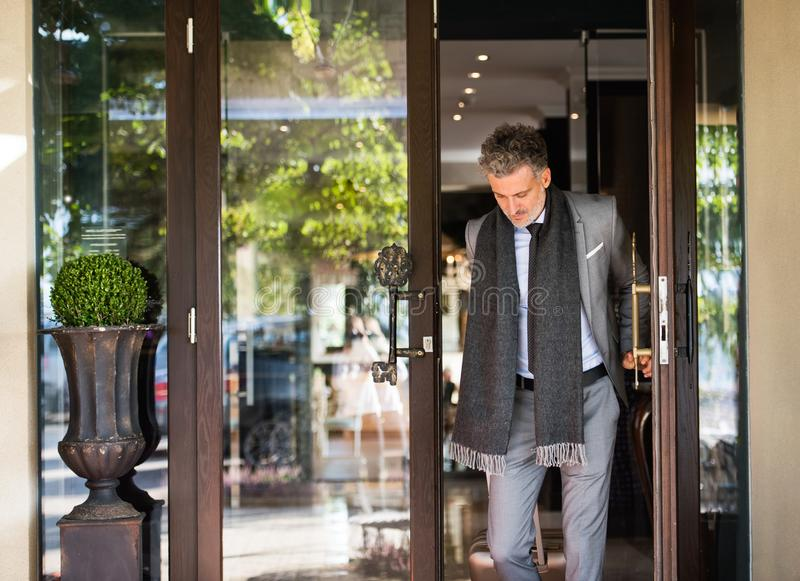 Mature businessman leaving hotel with luggage. Man walking out through the hotel front door royalty free stock photography