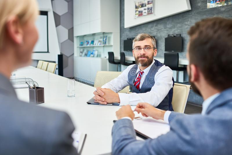 Mature Businessman Listening to partners in Meeting royalty free stock photos