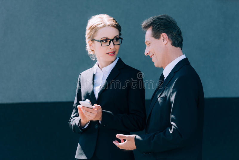 Mature businessman looking at blonde businesswoman using smartphone stock image