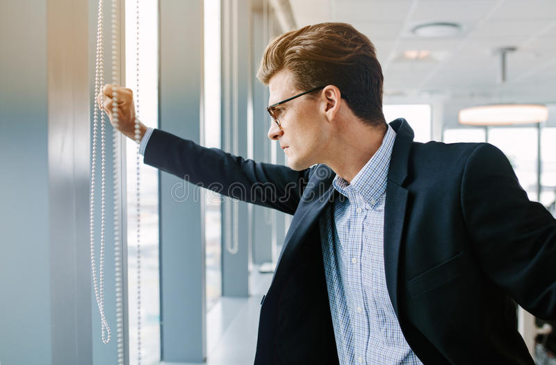 Mature businessman looking outside the office window. Side view shot of mature businessman standing in office. Caucasian male executive standing by window and stock photos