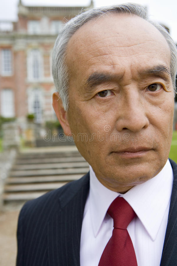 Mature businessman by manor house, portrait, close-up royalty free stock images