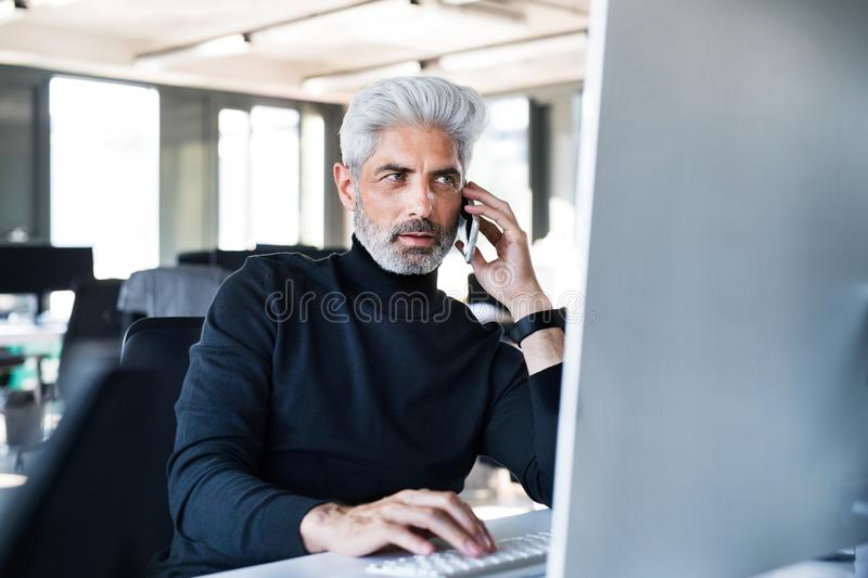Mature businessman in the office making a phone call. royalty free stock images