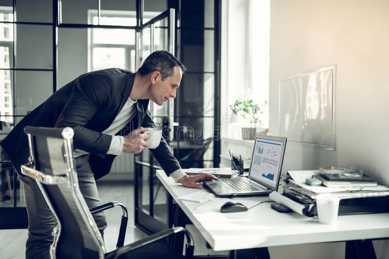 Mature businessman reading report on laptop while drinking coffee stock photography