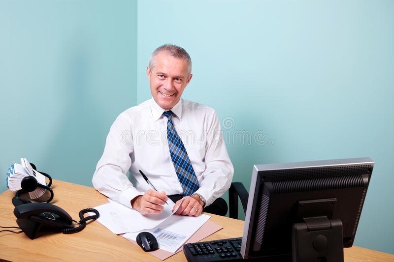 Mature businessman sat at his office desk. Mature businessman sat at an office desk working on some paperwork smiling to camera. The graphs and text on the stock image