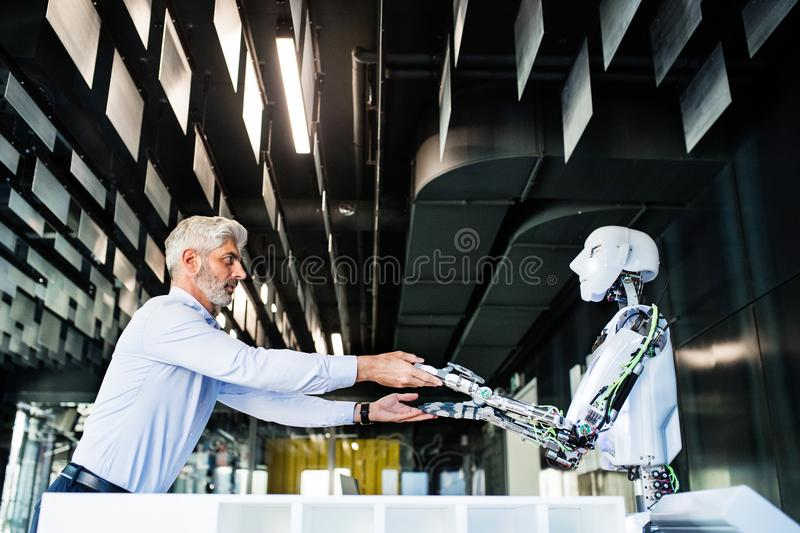 Download Mature Businessman Or A Scientist With Robot. Stock Image - Image of corporate, blue: 101471923