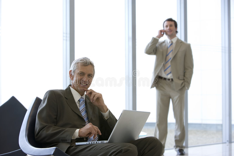 Mature businessman seated stock photos
