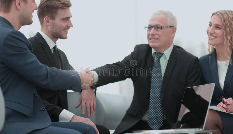 In a sign of cooperation, the partners shake hands after signing. Mature businessman shaking hands to seal a deal with his partner and colleagues in a modern stock photos