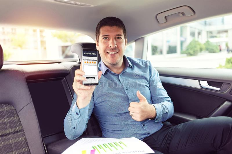 Mature businessman sitting on backseat of car rating taxi services on app while commuting to work – business on the go royalty free stock image