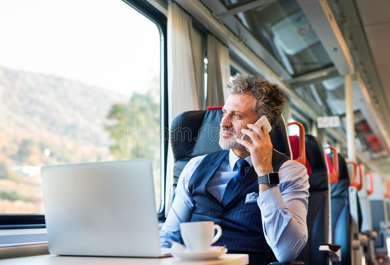 Mature businessman with smartphone travelling by train. stock photos