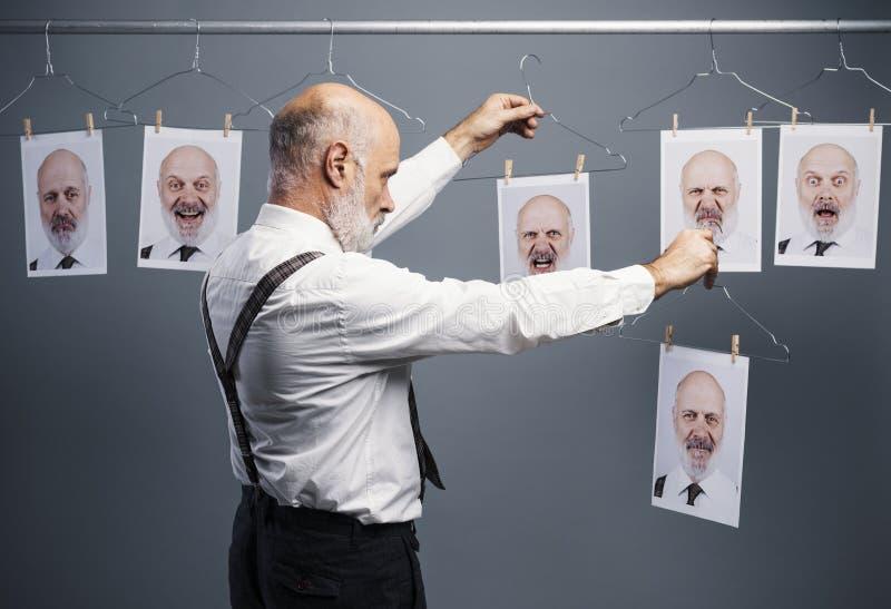 Senior businessman choosing his portraits royalty free stock images