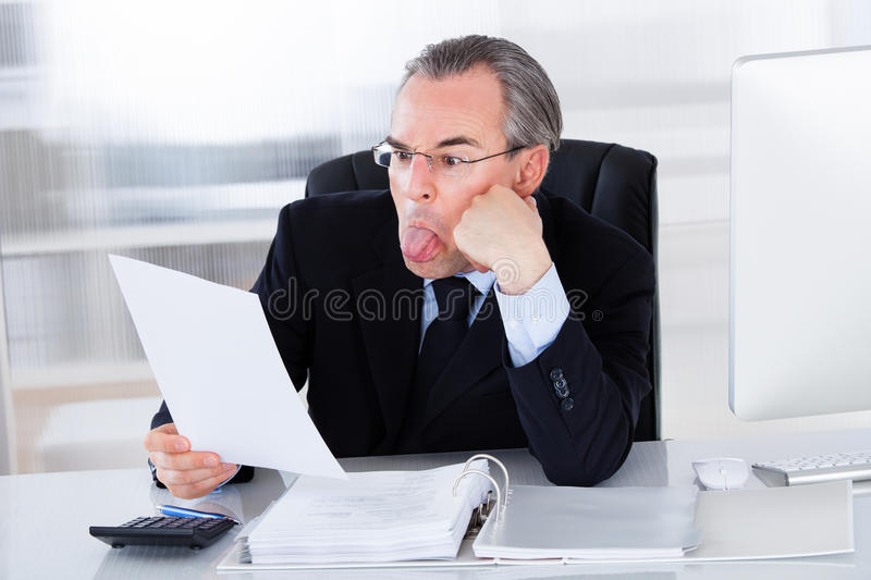 Mature Businessman Sticking Tongue Out royalty free stock images