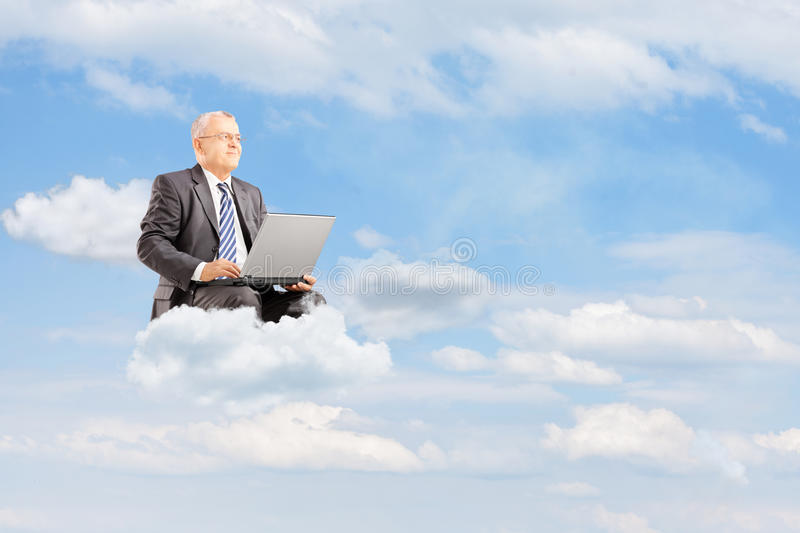 Mature businessman in suit flying on clouds with laptop outside royalty free stock images