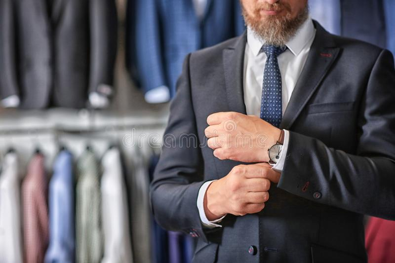 Mature businessman in suit with wristwatch in menswear store royalty free stock images