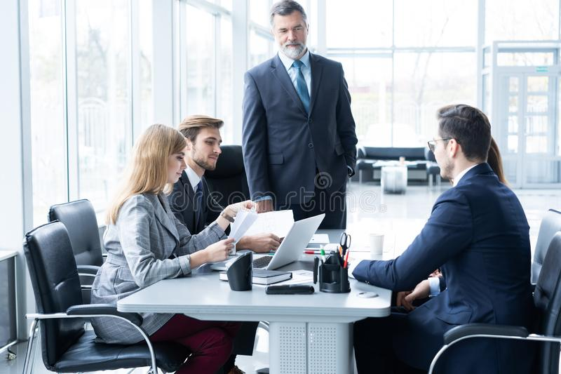 Mature businessman talking and explaining his business strategy to his colleagues at office. royalty free stock photos