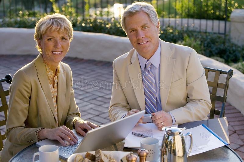 Mature businessman and woman sitting at outdoor restaurant table, businesswoman using laptop, smiling, portrait royalty free stock photography