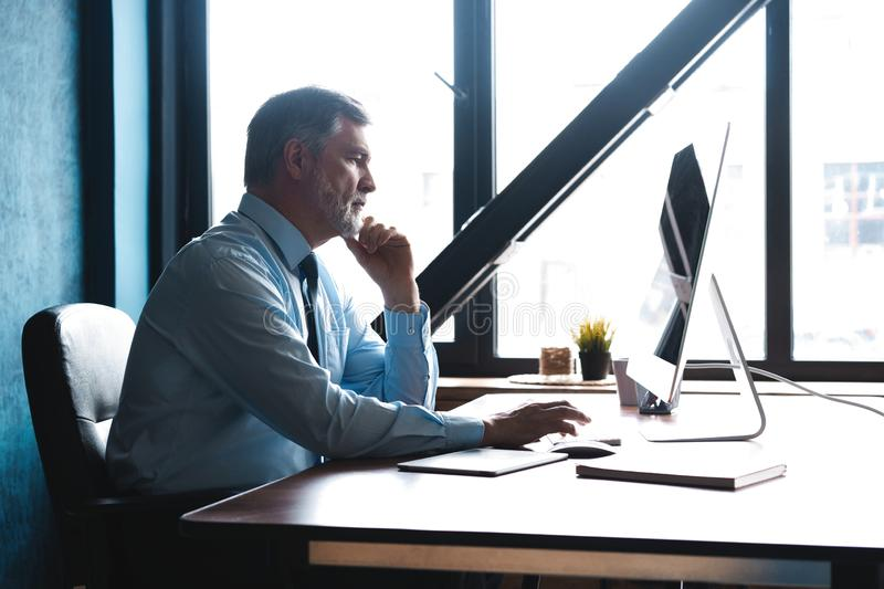 Mature Businessman Working On Computer In Office. Mature Businessman Working On Computer In Modern Office stock image